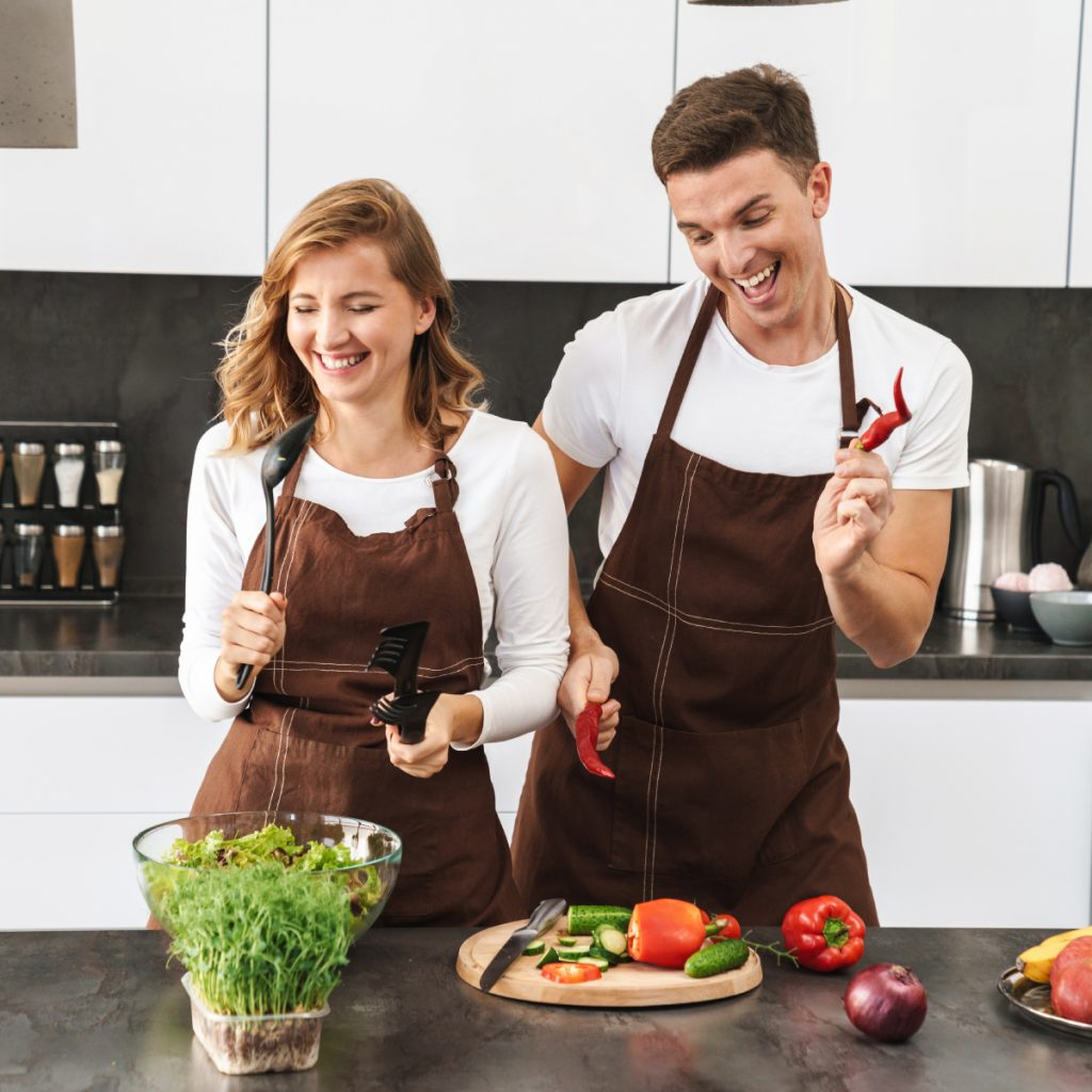 A man and women prepare food for their meal prep business in a kitchen wearing brown aprons.