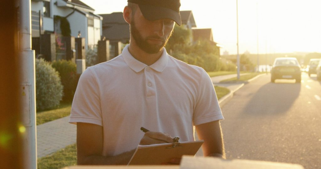 Man looks over delivery boxes while checking packaging slips.